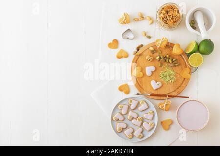 Preparare per il giorno di San Valentino. Iced piccante biscotti frollini nel cuore forme, abbellito con calce-lampone ghiaccio tritato e i pistacchi. La cottura wi Foto Stock