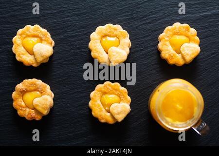 Valentine Holiday food idea concetto casalingo biologico rustico limone cagliata biscotti shortbread su sfondo nero Foto Stock