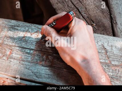 Una mano che tiene un coltello tascabile multitool rosso che scolpita una firma in un fascio di legno. Atto di vandalismo, delinquente