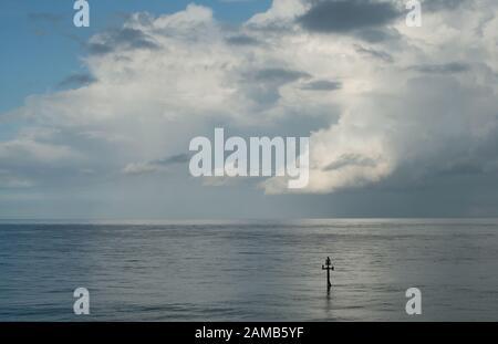Una classica scena minimalista di mare, cielo azzurro orizzonte e nuvole delicatamente in movimento senza distrazioni catturate in una luce incantevole Foto Stock
