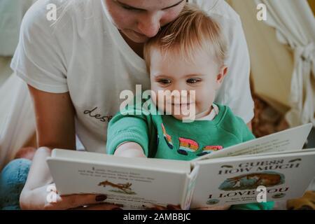 Bambino giovane che legge con la loro mamma