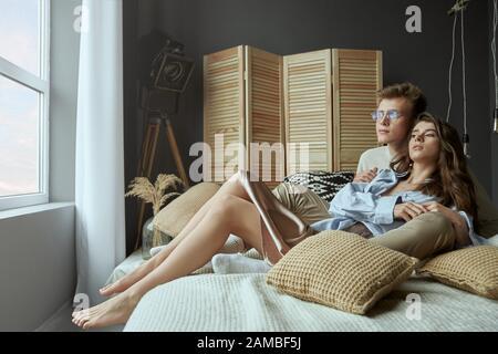 Vista frontale della dolce coppia giovane felice seduto e abbracciato sul letto a casa. Giovane ed elegante ragazza brunetta sdraiata e rilassante in braccia di ragazzo sorridente in occhiali. Concetto di amore, rapporto.