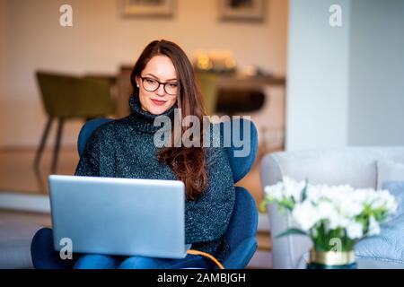Scatto di giovane donna sorridente che usa il suo laptop mentre sedendosi sulla sedia e lavorando dalla sede. Foto Stock