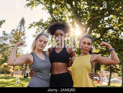 Amici femminili multietniche giovani e sportive che si flettono il loro muscolo guardando la macchina fotografica nel parco - donna forte che raffigura il potere femminile