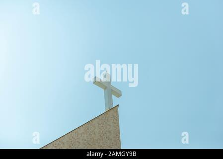 Colomba volare sopra una croce cristiana nella chiesa cattolica su uno sfondo blu cielo. Concetto di fede, di pace e di religione. Vista dal basso dalla croce della chiesa Foto Stock
