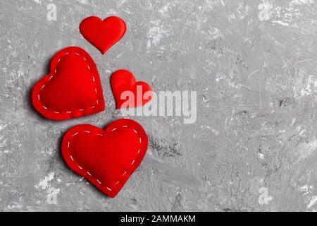 Vista dall'alto composizione dei cuori rossi su sfondo cementizio. Concetto di relazione romantica. Il giorno di Valentaine.