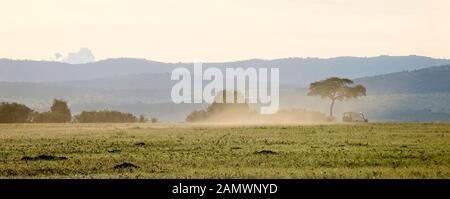 Un safari veicolo invia polvere come unità su un asciutto il Masai Mara, Kenya.