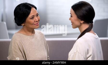 Madre che parla con la figlia, teneramente guardandola, dando consigli, maternità