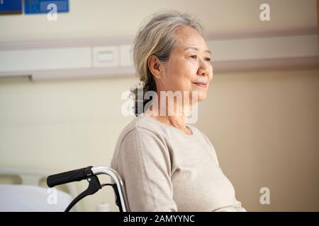 contenuto asian anziano donna seduta in sedia a rotelle nella sua stanza in casa di cura con espressione facciale pacifica