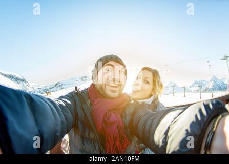 Coppia giovane rendendo selfie neve montagna resort lo sfondo con il telefono cellulare - Tourist ridendo e rendere divertente facce emozionali nella fotocamera dello smartphone Foto Stock