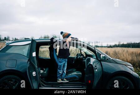 ragazzo in piedi su una macchina elettrica che guarda fuori la campagna Foto Stock