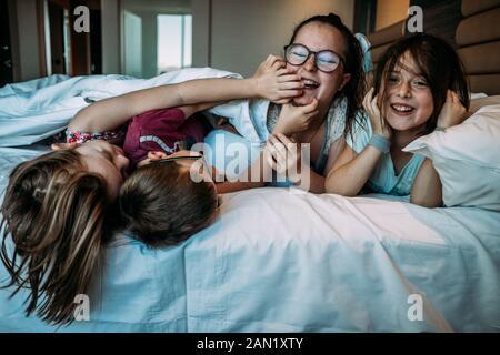 i bambini che giocano sul letto dell'hotel mentre sono in vacanza Foto Stock