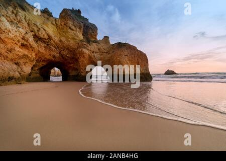 Praia João de Arens, con grotte al crepuscolo. Foto Stock