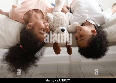 Felice nero fratello e sorella recante capovolto sul letto. Foto Stock