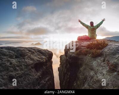 Giovane donna sedersi sulla cima di una montagna celebrare la giornata. Signora giovane escursionista in seduta verde blu giacca a vento con red zaino sulla scogliera taglienti