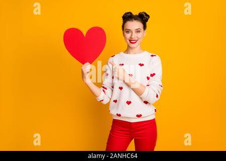 Foto di abbastanza affettuoso lady tenere la carta cuore mostra data cartolina indicando il dito promozione usura rosso bianco cuori pattern pullover pantaloni