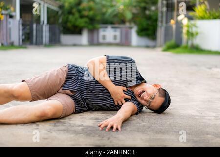 Uomo asiatico avente un attacco di cuore o insufficienza cardiaca a strada nel villaggio di casa. Petto addolorato sembrano essere avrà avuto un attacco di cuore da malattia. Healthcare M