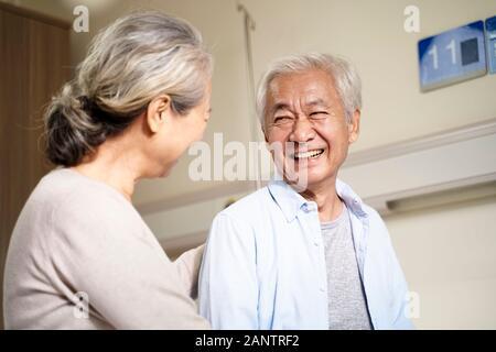 Felice asian coppia senior parlando in ospedale