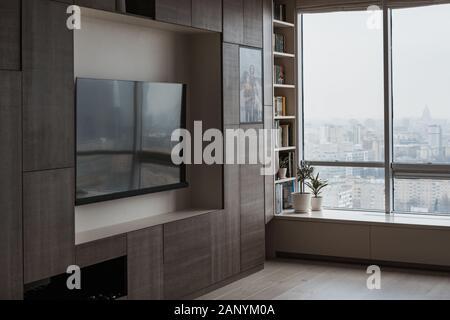 Arredamento in stile moderno e un grande schermo TV in soggiorno moderno con finestre panoramiche. Confortevole soggiorno.
