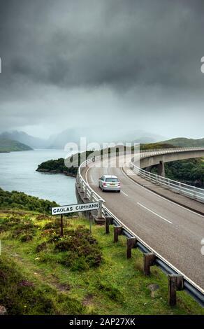 Guida auto sul ponte Kylesku sul Loch un Chairn Bhain in Sutherland, Scozia, parte della costa Nord 500 percorso panoramico