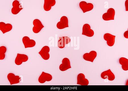 Cuori rossi sparsi su un sfondo rosa con spazio libero per il testo