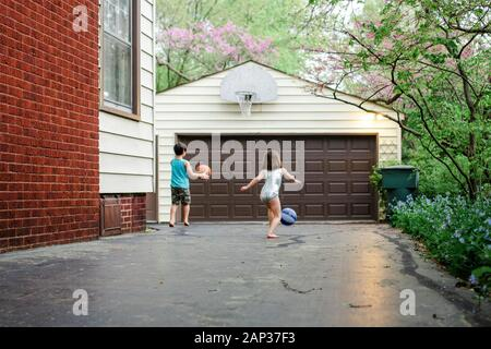 Due bambini giocano a basket insieme nel vialetto al crepuscolo Foto Stock