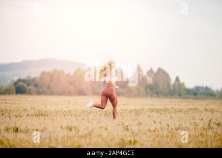 Giovane donna bionda runner in abbigliamento sportivo corre su campo parco fuoristrada