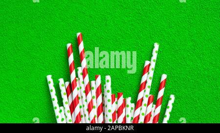 Un sacco di tubi rossi per il succo su uno sfondo verde. Foto Stock