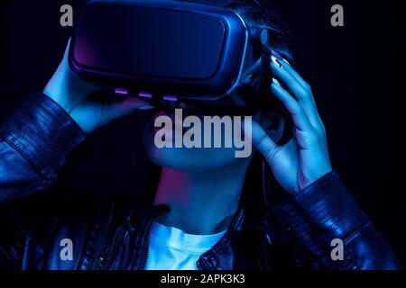 Giovane ragazza afroamericana che gioca con occhiali VR, godendo di un visore per realtà virtuale a 360 gradi per il gioco, isolato su sfondo nero in neo Foto Stock