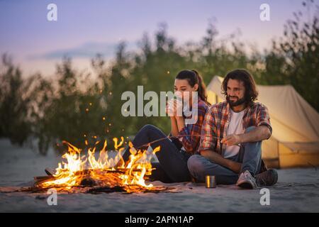 Giovane coppia amorevole di turisti camping, seduta vicino a un falò contro la tenda e bere il tè una tostatura marshmallow su una spiaggia di sera. Attraente razza mista ASIATICHE TURISTICHE Caucasica ragazza e barbuto uomo bello in appoggio avendo divertimento vicino al fuoco in camicia casual e jeans all'aperto sulla natura. Turismo e concetto di viaggio foto Foto Stock