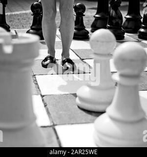 Immagine in scala di grigi di una femmina in piedi al centro di una grande scacchiera
