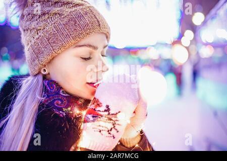 La ragazza tiene vetro di cartone con caffè o tè caldo in inverno in mitens caldi Foto Stock