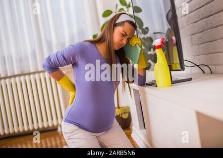 Donna incinta stanco che ha dolore nella parte posteriore mentre sta pulendo la sua casa.