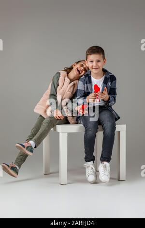 Cute elegante piccola coppia bambino ragazza e ragazzo con cuori rossi su bastone in abiti alla moda siotting insieme in studio. Moda bambini concetto. San Valentino. Foto Stock