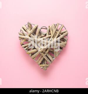 Concetto creativo vacanza San Valentino amore foto di cuore fatto a mano di bastoni su sfondo rosa.