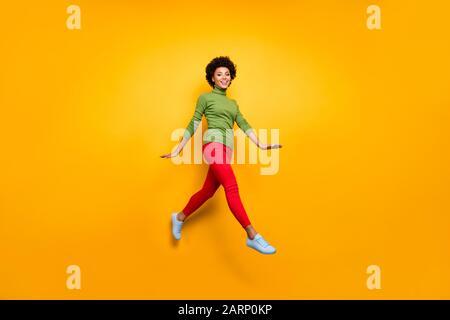 Corpo intero dimensione girato foto di ricci bruna ondulata capelli ragazza che corre saltando in pantaloni rossi scarpe bianche isolato vivido sfondo di colore Foto Stock