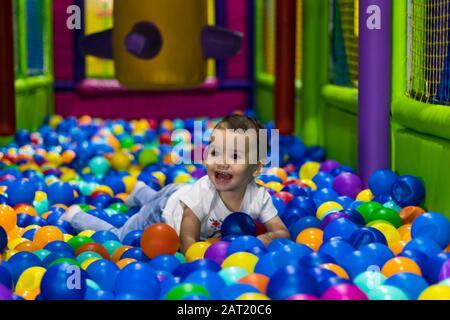 Una bambina carina e felice ridendo e giocando in un parco giochi al coperto in un centro commerciale a Dubai, Emirati Arabi Uniti. Foto Stock