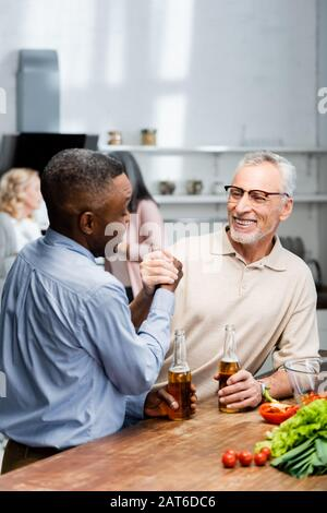 l'uomo afroamericano tiene le mani e parla con un amico sorridente in cucina