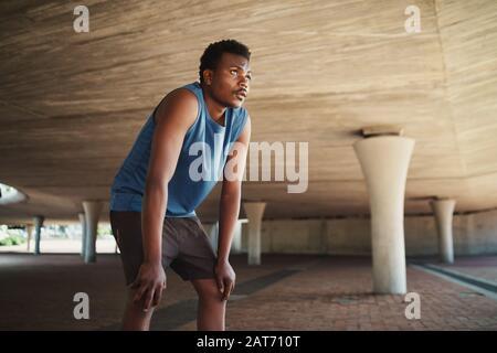 Corridore maschio esausto che prende un riposo dopo aver eseguito duro sulla strada sotto un ponte di cemento