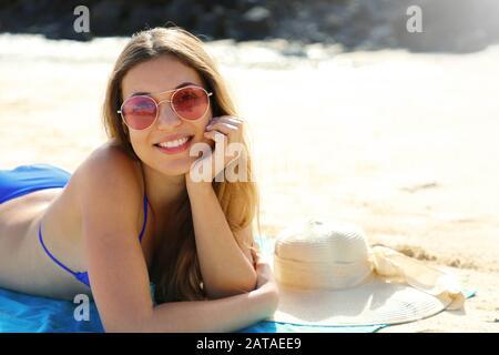 Giovane bella donna sorridente godendo relax sdraiata sulla spiaggia guardando la macchina fotografica. Concetto di vacanze estive. Foto Stock
