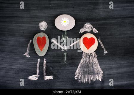 Ciottoli con cuori rossi dentro disegno di gesso di uomo e donna che tiene fiore nelle mani su lavagna. Primo piano.