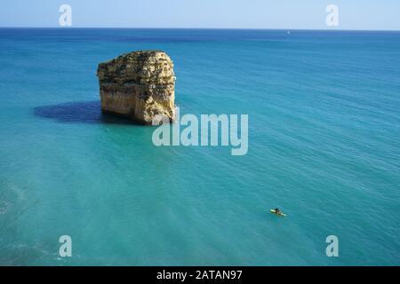 GIOVANE UOMO SU UNA TAVOLA DA PADDLEBOARD VICINO A UNA MAESTOSA PILA DI MARE (VISTA ELEVATA). Praia Do Barranquinho, Lagoa, Algarve, Portogallo. Foto Stock