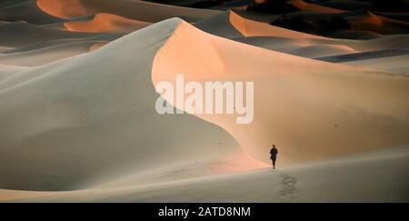 Donna che cammina nelle dune di sabbia, Mesquite Flat Sand Dunes, Death Valley, California, USA