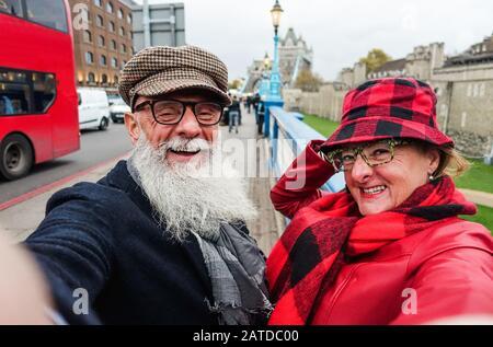Felice coppia senior prendere selfie a londra - Old trendy persone divertirsi con le tendenze della tecnologia - viaggio e gioioso anziani stile di vita concetto - Main