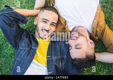 Ritratto di giovane coppia gay trascorrere un bel tempo e sdraiato sull'erba al parco. LGBT e concetto di amore. Foto Stock
