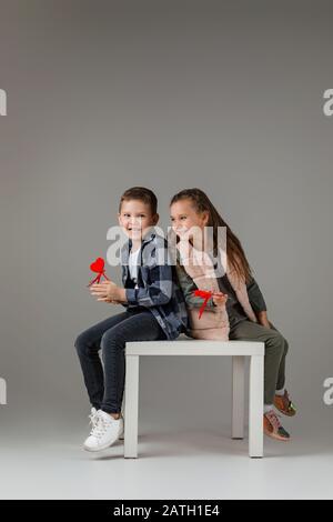 felice elegante piccola coppia bambino ragazza e ragazzo con cuori rossi su bastone in abiti alla moda che siotting insieme in studio. moda bambini concetto. San Valentino. Foto Stock