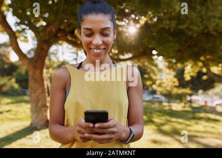 Ritratto di una giovane donna sorridente sportiva utilizzando il cellulare nel parco prima di fare esercizio Foto Stock