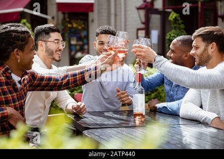 Un gruppo di amici maschi che hanno un brindisi celebrativo insieme all'aperto in una birreria all'aperto della città. Foto Stock