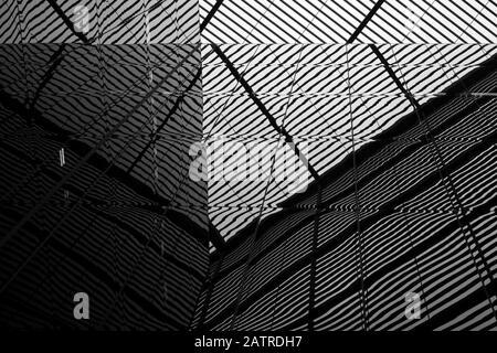 Architettura moderna astratta vista prospettica a basso angolo di una facciata astratta in vetro specchiato che riflette come concetto di composizione simmetrica surreale. Foto Stock