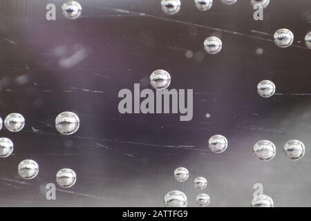 Macro colpo di primo piano di bolle visto attraverso il vetro in una tazza di acqua. Foto Stock